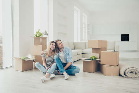 Mortgage relocation cardboard package new idyllic ideal life real estate concept. Portrait of glad cheerful peaceful tranquil people enjoying bonding sitting on floor looking at coopy-space Stockfoto