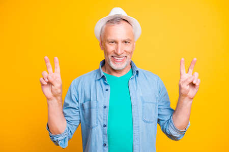 Happiness good day mood concept. Close up photo portrait of handsome confident cute sweet in green t-shirt old gentleman demonstrating victory sign with hands isolated on bright vivid background