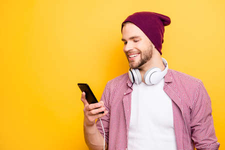 Profile side half-faced close up portrait of handsome excited cheerful joyful satisfied glad guy with toothy beaming smile using smartphone in hands listening to track tunes isolated background