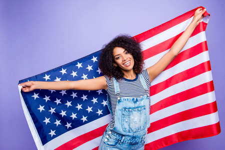 Portrait of cheerful positive girl in denim outfit showing american flag looking at camera isolated on bright violent background. Holiday concept Stock Photo