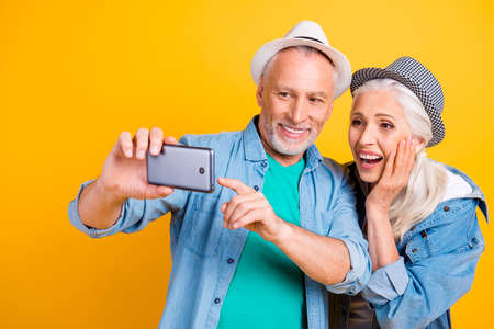 Modern technology emotion expressing concept. Close up photo portrait of funny funky crazy excited cheerful partners watching extreme sport video on telephone in hand isolated on bright background Stock Photo