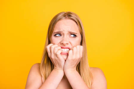 Woman with nervous expressions face, keeps hands near mouth and stare with big eyes against yellow background. Studio shot of frightened young woman, people and fear concept