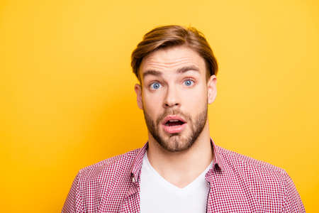 Close up portrait of handsome excited cheerful joyful attractive amazed funny with big eyes entrepreneur wearing red checkered shirt and white t-shirt isolated on bright yellow background copyspace Stock Photo