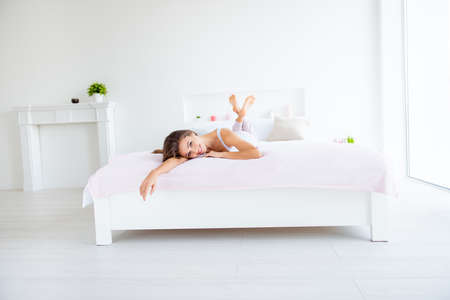 Full size portrait of sensual tender woman lying on stomach in bed enjoying recreation in modern white room with interior looking at camera day health healthy life Zdjęcie Seryjne