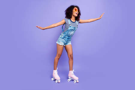 Full body portrait of positive funky girl learning to ride on roller skates keeping balance enjoying activity isolated on bright violent background retro vintage quad student concept