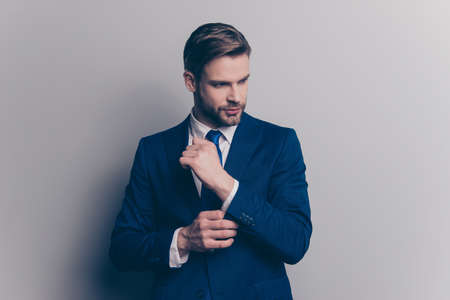 Portrait of stunning, fashionable, cool, rich man with stubble in blue suit correcting button on cuffs of sleeve of white shirt with arm, looking to the side, isolated on grey background