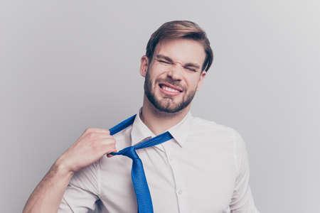 Schließen Sie herauf Porträt des erschöpften frustrierten gestressten gutaussehenden traurigen unglücklichen verärgerten Unternehmers, der versucht, unbequeme blaue Krawatte formelle Abnutzung lokalisiert auf grauem Hintergrundkopierraum zu entfernen Standard-Bild