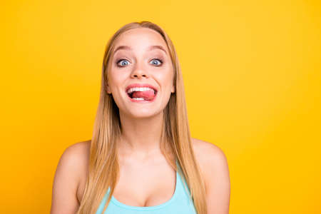 Happy joyful and funky blonde girl showing tongue and make big smile. Attractive young woman is posing on the camera isolated on yellow background