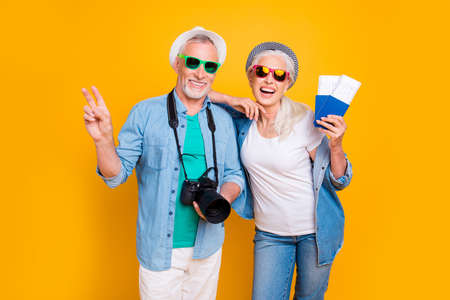 Tourismus Touristen Reisende Reise Ruhe Wochenende Urlaub Urlaub entspannen Konzept. Fotoporträt des aufgeregten Kerls zwei Finger Digicam Dame VIP Passagiere, die Dokument mit Tickets isolierten Hintergrund zeigen Standard-Bild