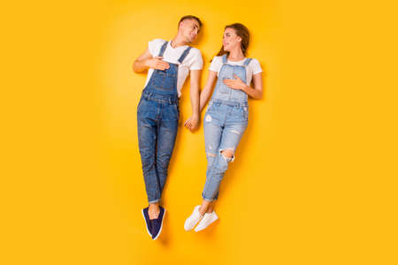 Siblings spouses friendship denim sneakers concept. Overhead view full length body size photo portrait of two cute sweet lovely beautiful guys holding hands on chest isolated on bright background Stok Fotoğraf