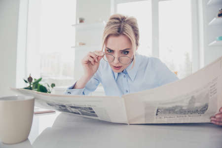 Adult adorable woman lady boss putting spectacles down keeping in hands and reading newspaper early in the morning having a drink in kitchen