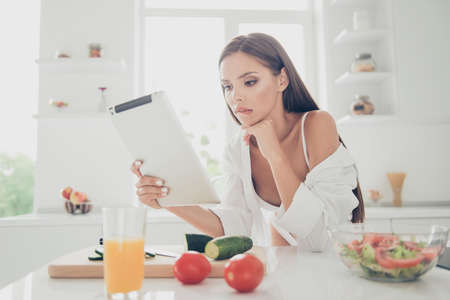 Attractive and sexy young woman on white lingerie and long shirt with naked shoulder sit in thought, look at the tablet and biting lower lip. Kitchen with cutting board, ingredients for salad and juice on the table Imagens