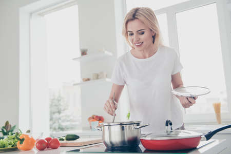 Adorable attractive beautiful adult smiling cheerful woman wearing pajama white t-shirt cooking stirring food in pot with spoon. Red tomatoes green salad chopped cucumber yellow pepper lying on table Reklamní fotografie