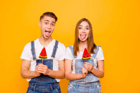 Young beautiful cute adorable cheerful couple grimacing holding water melon candies in their hands, smiling, looking straight, showing tongues out over yellow background, isolated Imagens