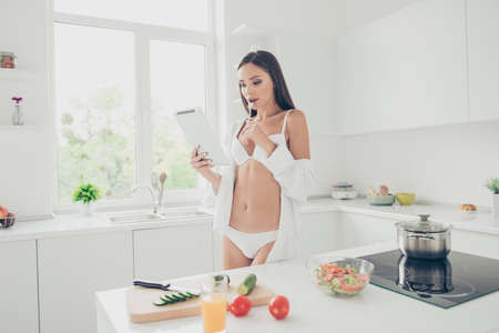 Hot brunette housewife with amazing body in white bra and panties look at the tablet thoughtfully holding fork in the mout. Girl reading recipe for a simple breakfast