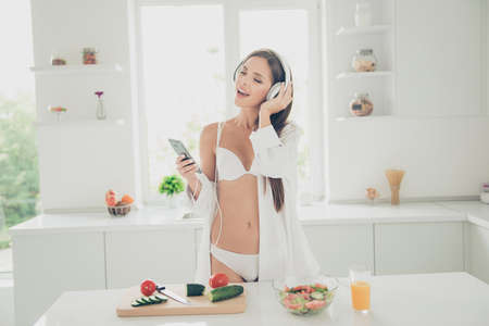Sensual young brunette in white lingerie and shirt with long sleeve, listening music through headphones and sings in the kitchen