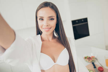 Close up portrait of naughty and sweet young brunette in white bra and shirt making selfie on her phones camera in here kitchen