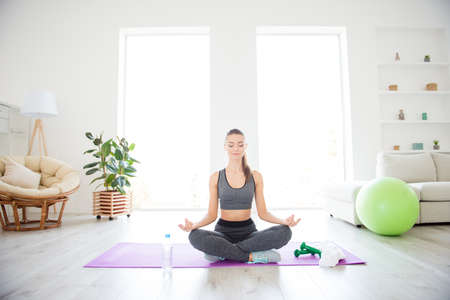I want my soul and mind to be clean! Portrait of beautiful attractive lady wearing grey tank top and leggings making om sign with fingers sitting with crossed legs on purple carpet against windows