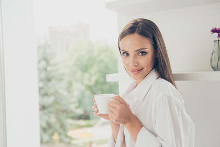 Close up portrait of young attractive lady in white shirt on a morning coffee break, she is resting and enjoying the drink, look at the camera and smiling