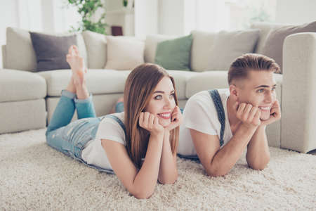 Portrait of young attractive cute couple in love wearing overall lying together on carpet bearfoot, smiling, in apartment