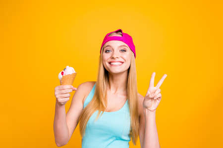 Portrait of young woman with blond hair, big blue eyes and toothy beaming smile. Positive girl holds an ice cream cone in her hands and demonstrating two fingers v-sign isolated on yellow background