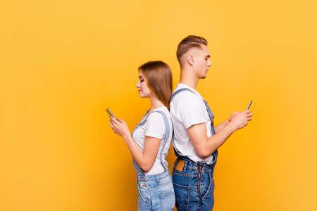 Porträt des niedlichen jungen Studentenpaares, das lässig trägt, Rücken an Rücken steht, ihre Smartphones in Händen hält, ernsthaft auf Bildschirme schaut, über gelbem Hintergrund, isoliert, Copyspace Standard-Bild