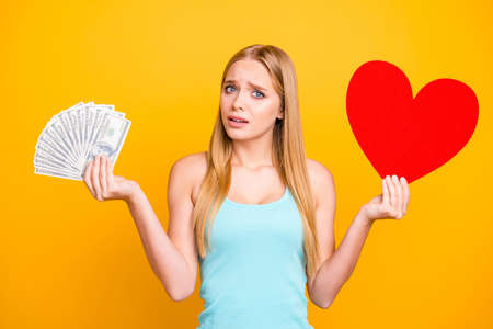 Young beautiful girl isolated on yellow background looks at the camera and hold money in one hand and big paper carton heart figure in other. Concept of difficult choice