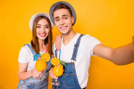 Self portrait of young beautiful happy students couple in love wearing hats drinking orange coctails, enjoying life of yellow background, isolated Stock Photo