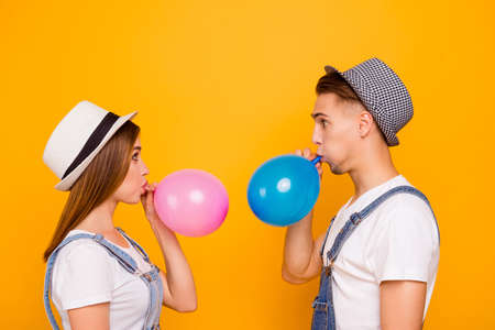 Young happy couple in love wearing hats blowing air balloons looking confused of yellow background, isolated