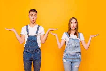 Portrait of cute young couple standing together, astonished with widely opened mouths, gesturing I do not know unsure sign, oops, problem, mistake, misunderstanding, isolated
