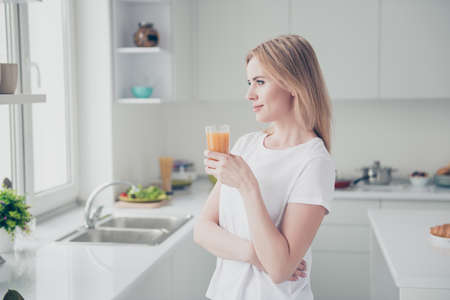 Portrait of adorable attractive beautiful cheerful smiling adult woman keeping glass of orange carrot juice in hand looking right at window standing in kitchen Banco de Imagens - 106118228