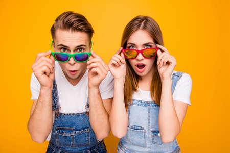 Hermosa linda pareja sorprendida adorable poniendo coloridos espectáculos 3d hacia abajo mostrando emoción wow sobre fondo amarillo, aislado