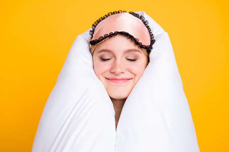 Portrait of funny and funky happy young woman with blindfellen on head and wrapped in white blanket, isolated on yellow background. Concept of a healthy sleep