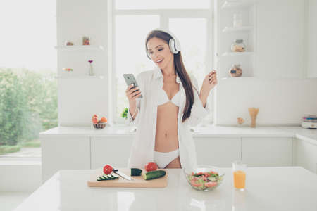 Charming and beautiful young woman in white lingerie and shirt, listening music through headphones, looking on the phone and holding fork on the hand cooking vegetable salad for breakfast