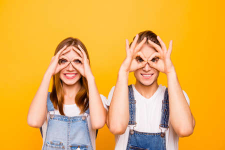 Close up portrait of playful young cute couple wearing casual, showing funny gestures looking through fingers okay sign over yellow background, isolated
