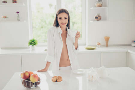 Successful and confident woman on a morning coffee break, resting and enjoying the drink. Young girl in white panties and long shirt with shoulder and chest stand on the kitchen of the house