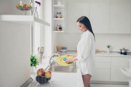 Hot brunette girl stands in front of sink in a long white shirt of early morning and wash the dishes on the bright light kichen