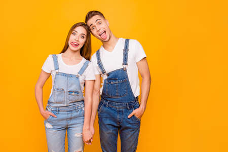 Portrait of funny fool playful lovely adorable young cute couple holding hands, showing tongues out, standing straight over yellow background