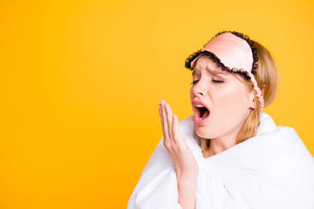 Girl wrapped in blanket and with eyemask on her head yawns closing her open mouth with her palm. The concept of healthy and comfortable sleep. Empty space for text on a yellow background