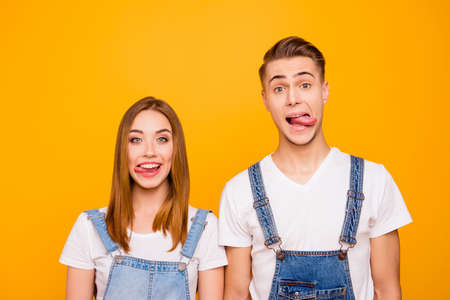 Close up portrait of funny playful lovely adorable young cute couple showing tongues out, looking straight over yellow background, isolated