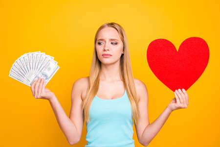 Young beautiful girl looks at the money in one hand and holds big paper carton heart figure in other. Concept of difficult choice isolated on yelow background