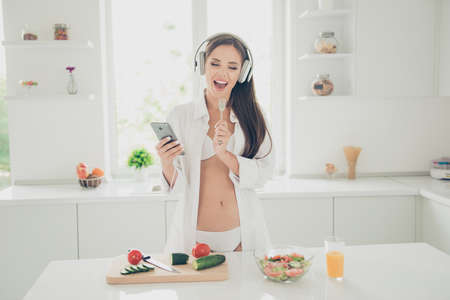 Good morning! Hot tempting and seductive woman in white lingerie and shirt with long sleeve, listening music through headphones and sings in the kitchen holds fork as a microphone