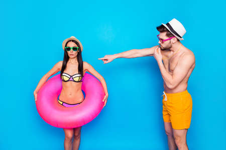 Be careful! Muscular man in yellow shorts for swimming blows into the whistle and shows at the excited girl in a colorful swimsuit which holds an inflatable lifebuoy around her waist 스톡 콘텐츠 - 106118375