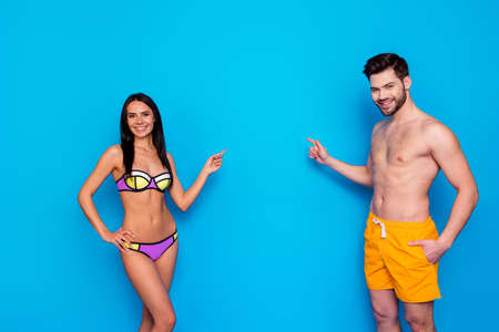 Happy and tan beautiful couple dressed at swimsuit showing with fingers on isolated blue background with copy space for text