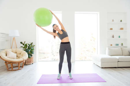 Beauty fashion wellbeing wellness vitality domestic light room good day lifestyle concept. Full length size photo portrait of beautiful glad nice pretty trainer raising green fitness ball above head