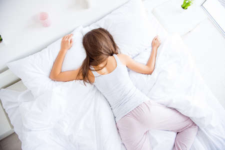 Haut de la page vue arrière portrait de femme endormie couchée sur le ventre portant des pantalons singulet fatigué après une dure journée