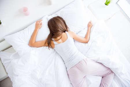 Porträt von oben von der verschlafenen Frau, die auf Bauch liegt und Hosenunterhemd trägt, das nach hartem Tag müde ist