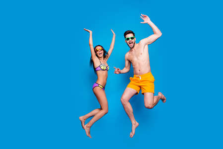 Full length portrait of a joyful young woman and happy man in sunglasses, dressed in swimsuit, jumping and putting hands up over blue background