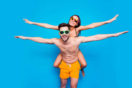 Happy man in sunglasses and yellow shorts keep on back charming young woman holding hands to side making airplane isolated on blue background