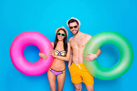 Concept of summer vacation and honeymoon. Guy and girl dressed in beachwear hold inflatable life ring standing isolated on blue background